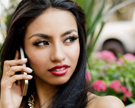 Beautiful woman sitting outside  talking on cell phone