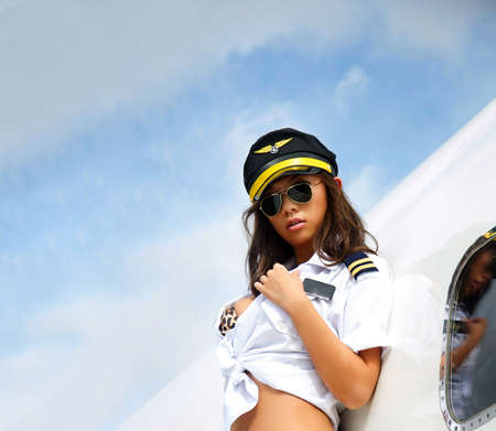 Beautiful model wearing crew hat beside plane with sky background for copy space 免版税图像