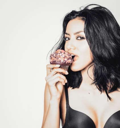 Beautiful woman desiring cupcake holding to mouth