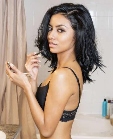 Beautiful woman doing her morning makeup routine 免版税图像