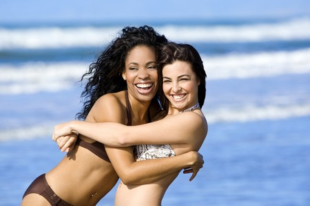 best: Two happy beautiful friends playing on the beach Stock Photo