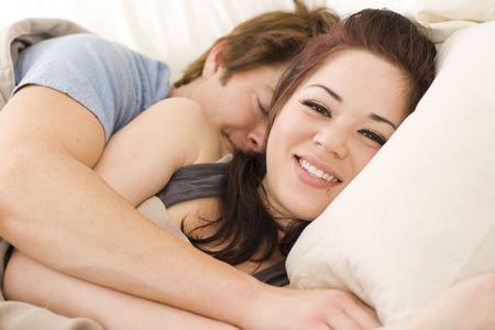 besos apasionados: Pareja feliz en la cama, por la que se