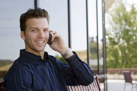 buiding: Happy business man on a call outside his office buiding