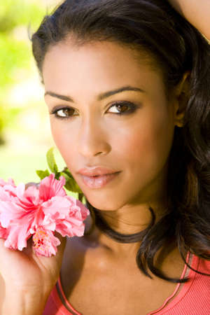 Beautiful exotic woman with a red hibiscus photo