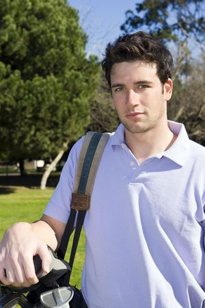Young man holing his golf clubs Banque d'images