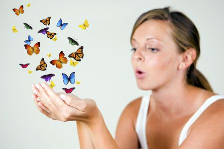 Girl blowing butterflies out of her hand