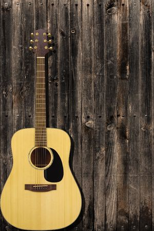 Classic guitar leaning on a wooden fence Stock Photo