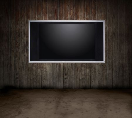 Dark grungy room with a wooden wall and a flat panel TV Stock Photo
