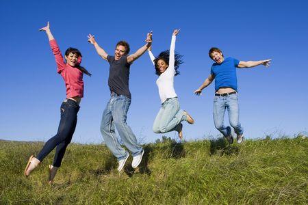 persona saltando: Diverso grupo de amigos que juegan en un brillante d�a soleado