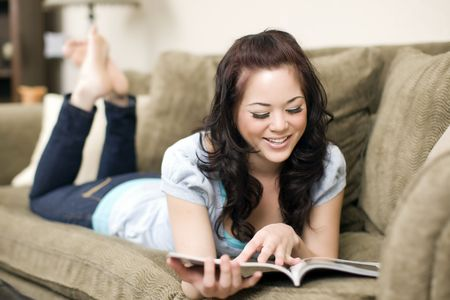 woman on couch: Pretty young woman lounging on a couch with a magazine