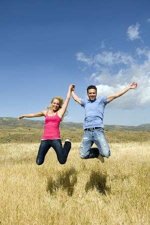 endearing: Young couple holding hands and jumping Stock Photo