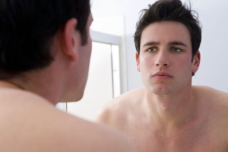 soft skin: Man looking at his reflection Stock Photo