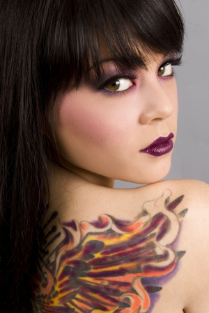 tatuaje de aves: Hermosa mujer con colores ex�ticos tatuaje Foto de archivo