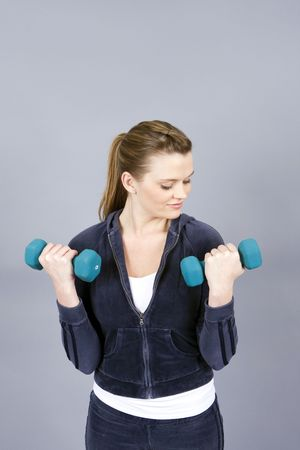 repetition: Pretty young woman exercising with free weights Stock Photo