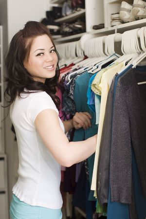 closet: Woman looking at clothes in a closet Stock Photo