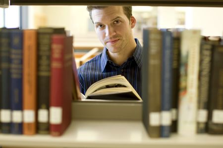 young boy smiling: Happy young man researching info at a library
