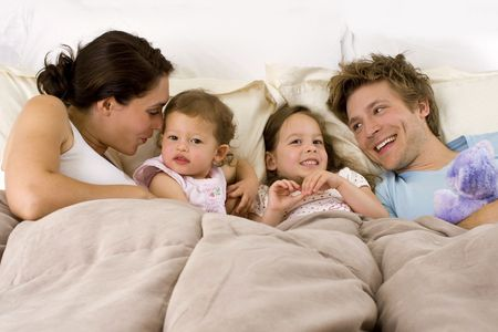 Happy family laying in bed photo
