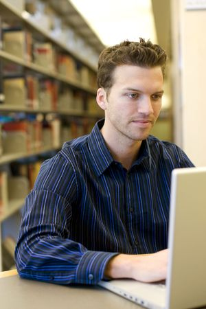 Nice young man researching information on a laptop photo