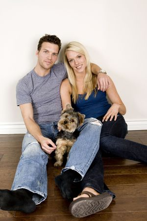 Attractive young couple sitting in their new home with their dog photo