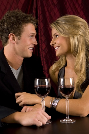 Attractive young couple drinking wine photo
