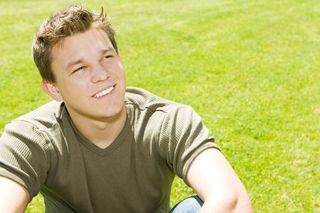 Young man sitting in the grass photo