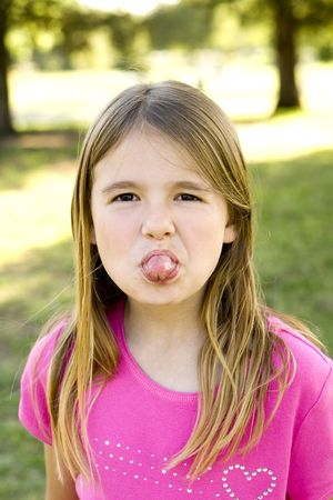 Cute little girl sticking out her tongue photo