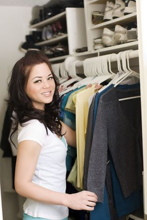 Woman looking at clothes in a closet photo