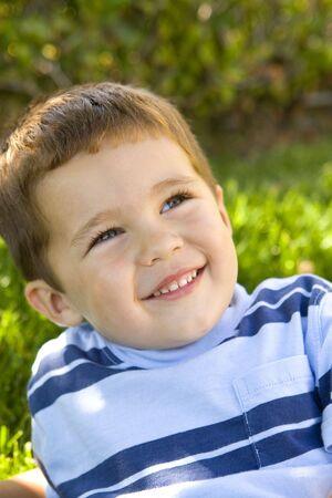 Cute kleiner Junge sitzt im Gras Standard-Bild