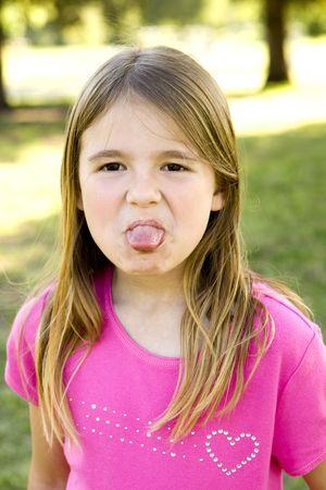 Cute little girl sticking out her tongue Reklamní fotografie