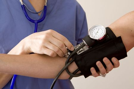 Doctor or nurse taking a patients blood pressure Stock Photo