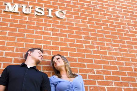 Attractive couple standing against a brick wall photo