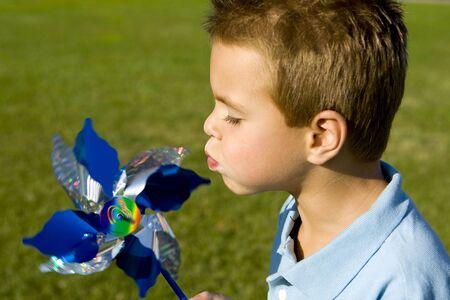 Little boy blowing on a pinwheel photo