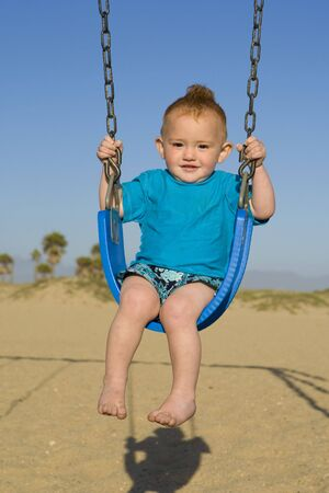 Toodler at the beach on a swing photo