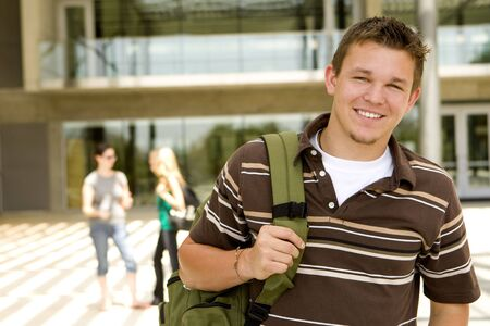 highschool: Young man at school holding a book bag