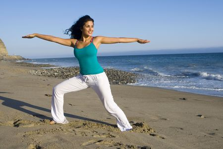 Young woman in a yoga pose at the beach