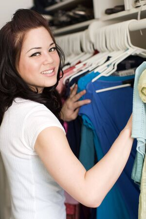 clothes rack: Woman looking at clothes in a closet Stock Photo