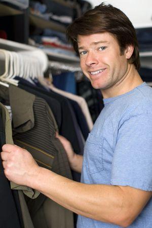 Man sucht durch T-Shirts in seinem Schrank Lizenzfreie Bilder