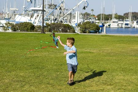 man flying: Little boy running with a kite Stock Photo