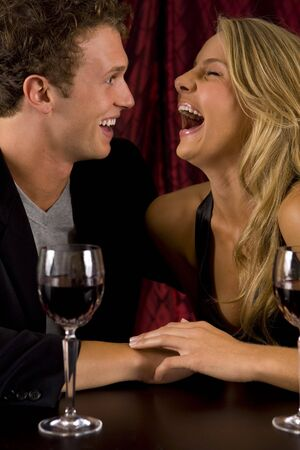 Attractive young couple laughing and drinking wine photo