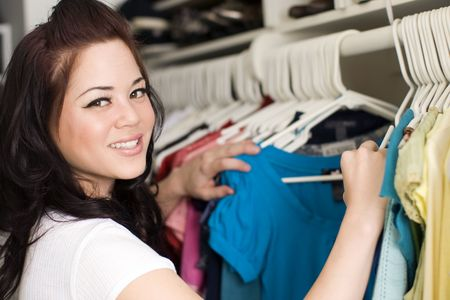 Woman looking at clothes in a closet Stockfoto