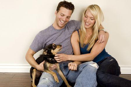 Attraktives junges Paar sitzt in ihrer neuen Heimat mit ihrem Hund Lizenzfreie Bilder