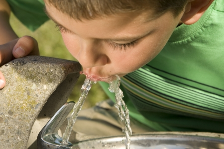 Little boy drinking from a fountain Stock Photo