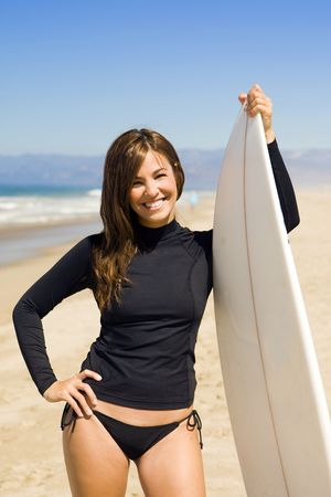Beautiful young woman at the beach with surfboard photo