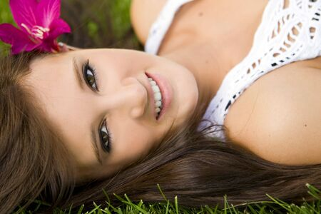 Attractive young girl sitting in the grass  photo
