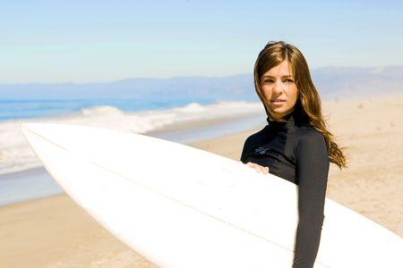 서핑 보드와 해변에서 아름다운 젊은 여자 스톡 콘텐츠