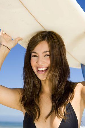 Schöne junge Frau am Strand mit surfboard