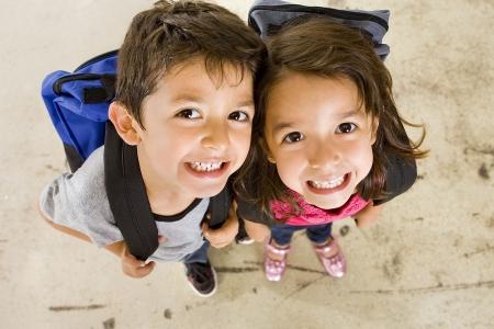Kleinen Jungen und Mädchen mit Ihrem Buch-Taschen  Standard-Bild
