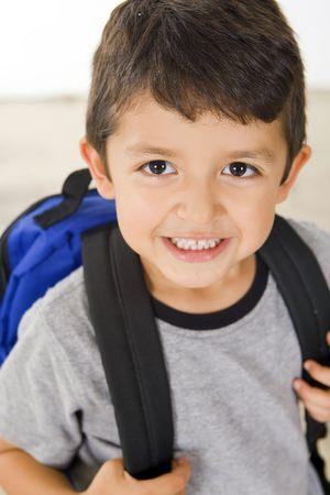 Kleiner Junge mit seinem Buch-Tasche
