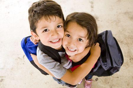 Wenig jungen und Mädchen mit ihren Buch-Taschen Standard-Bild