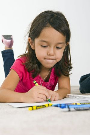 crayon drawing: Little girl laying on the carpet coloring Stock Photo